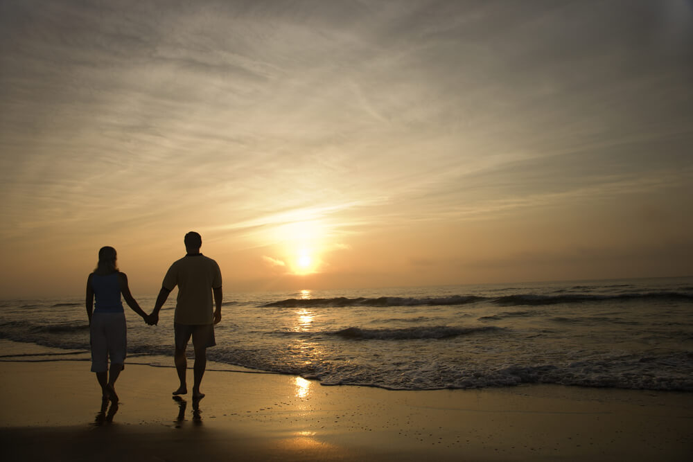 couple walking on beach while sunset